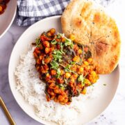 Overhead shot of spinach and chickpea curry with rice and naan in a white bowl