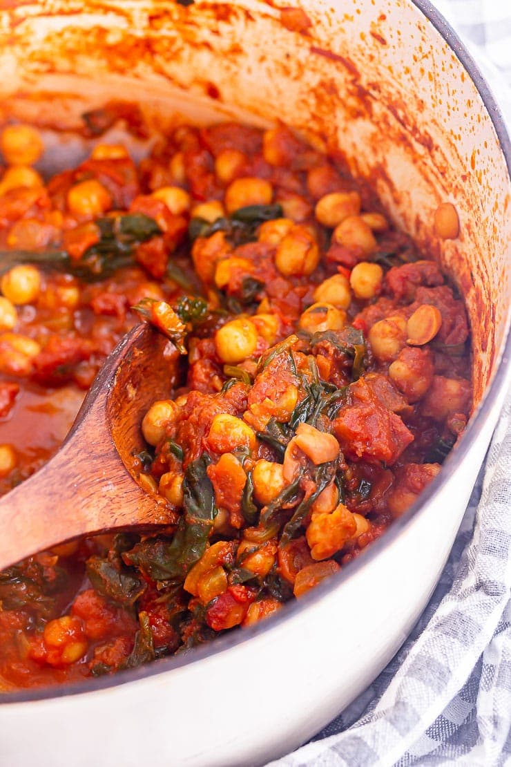 Wooden spoon in chickpea spinach curry in a white pot