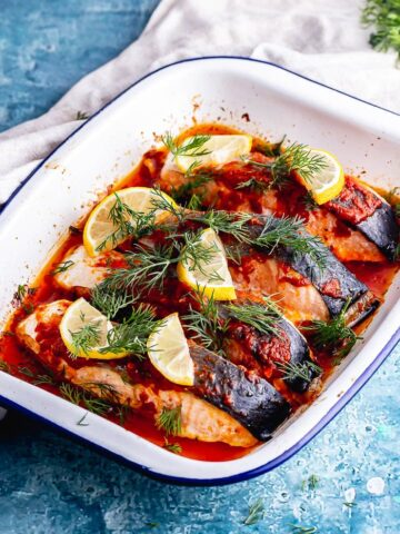 White baking dish with harissa salmon and lemon on a blue surface