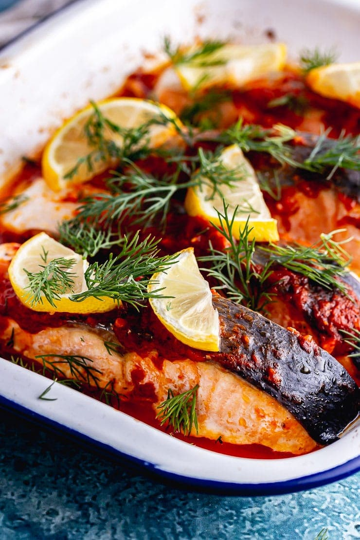 Close up of roasted salmon in a white baking tray with dill and lemon slices