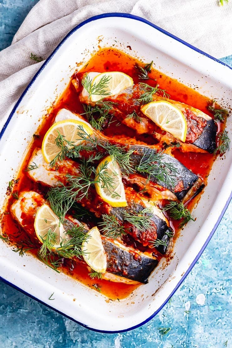 Overhead shot of a white falconwear enamel dish with harissa baked salmon topped with lemon