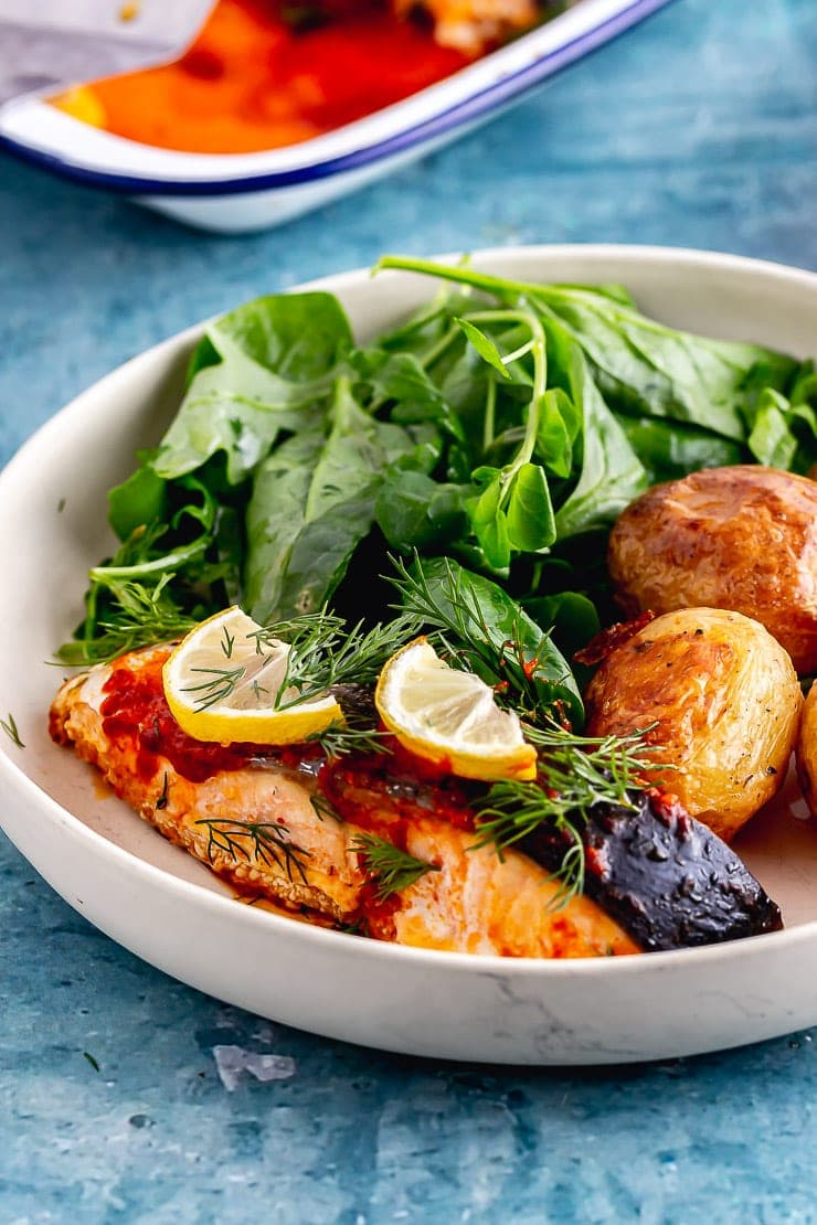 White bowl of roasted salmon with potatoes and salad