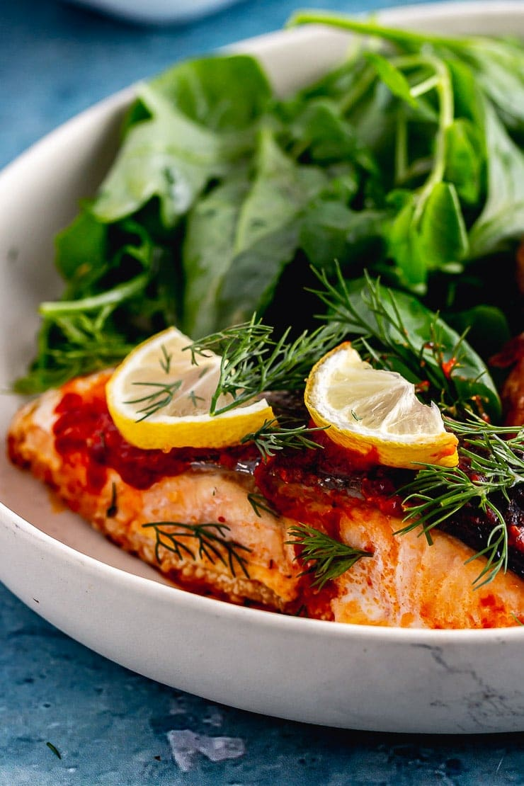 Close up of spicy roasted salmon with salad in a white bowl