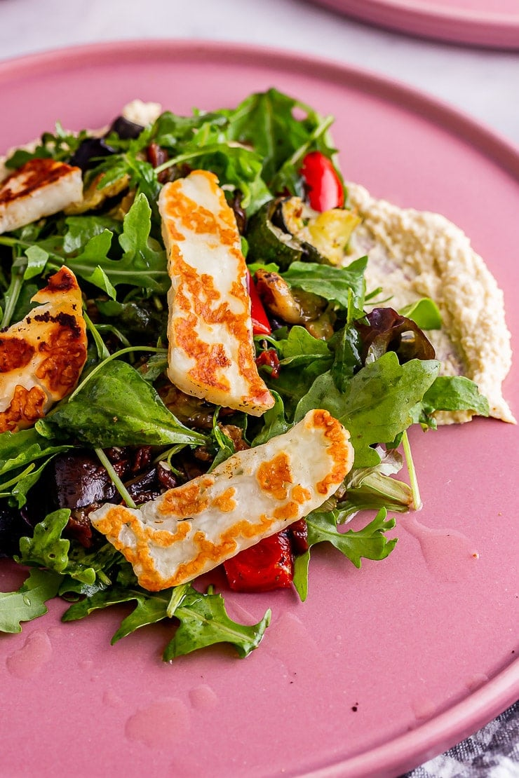 Close up of halloumi and vegetable salad with hummus on a pink plate