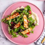 Overhead shot of pink plate of roast vegetable salad with halloumi on a marble background