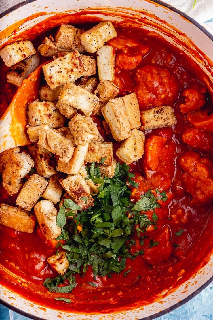 Close up of crispy tofu in a red curry sauce