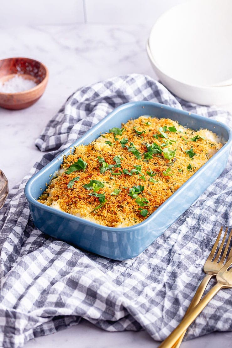 Blue baking dish with truffle mac and cheese on a checked cloth with gold forks