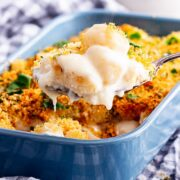 Side on shot of spoonful of gnocchi mac and cheese above a blue baking dish