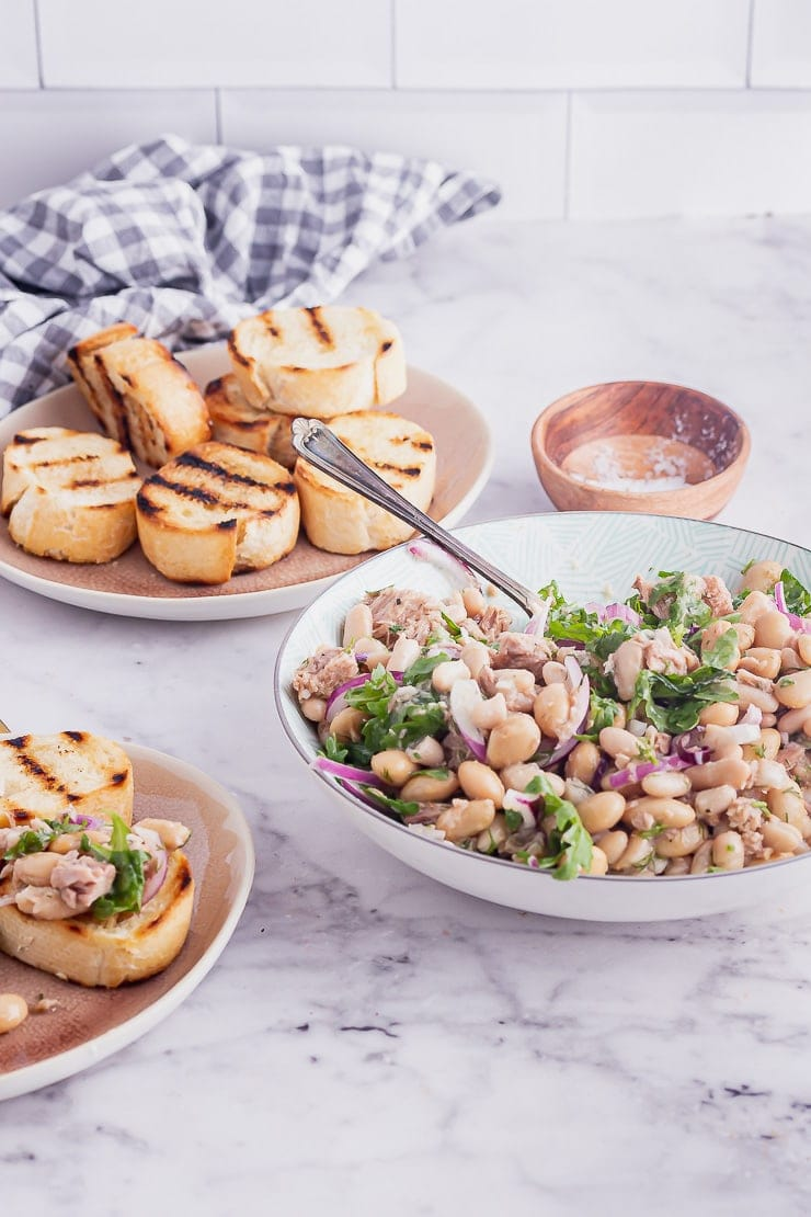 Bowl of tuna and bean salad with a spoon and garlic toasts on a marble background