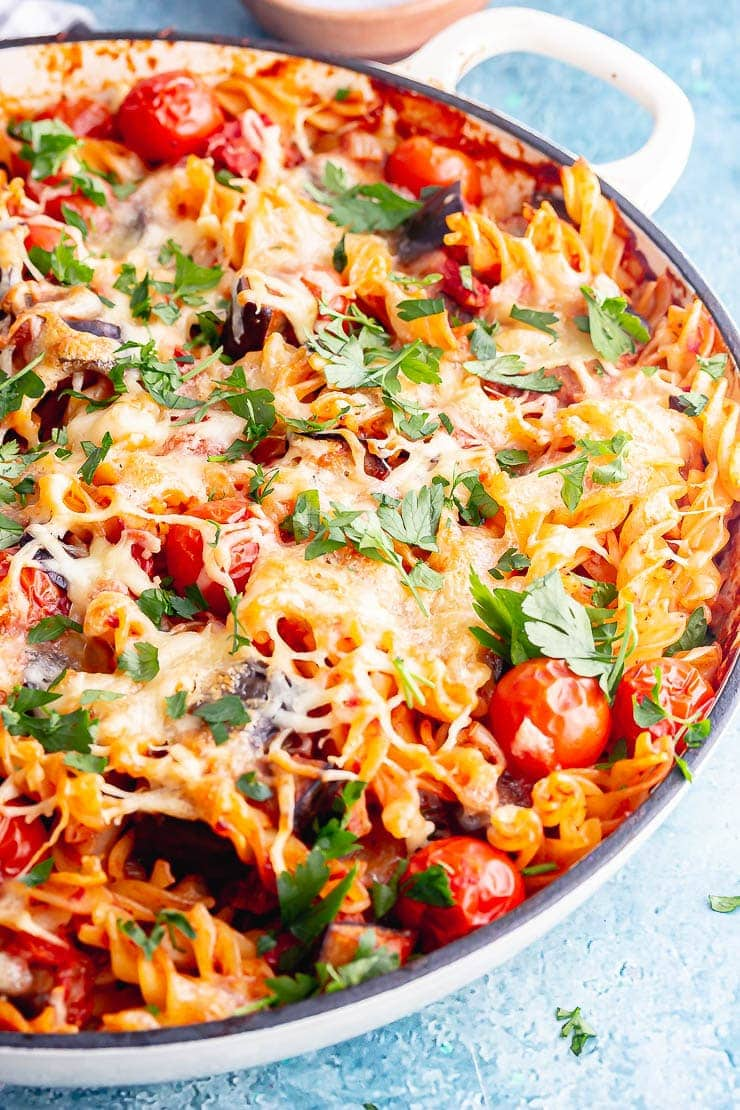 White dish of aubergine pasta bake on a blue background