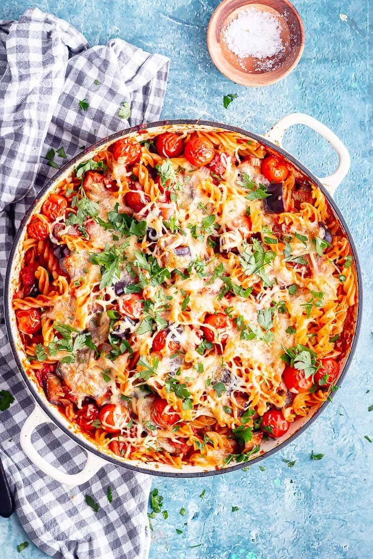 Overhead shot of aubergine pasta bake in a white dish on a blue background