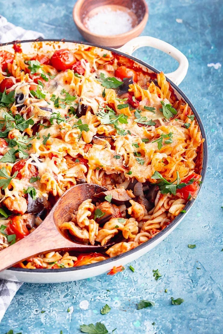 Wooden spoon in a dish of eggplant pasta with mozzarella