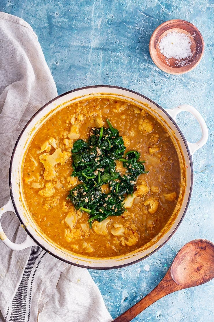 Overhead shot of lentil curry in a white pot on a blue surface