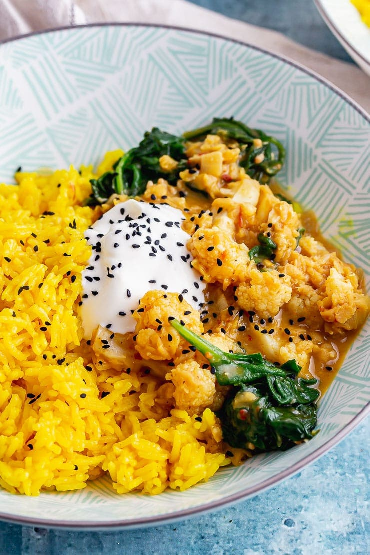 Close up of cauliflower curry with yoghurt and nigella seeds in a green bowl