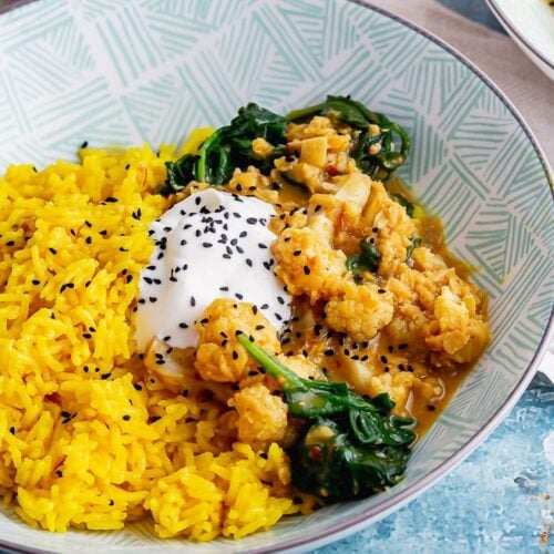 Lentil cauliflower curry with yoghurt and spinach on a blue background