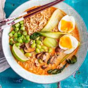 Overhead shot of coconut curry ramen with chopsticks in a blue bowl