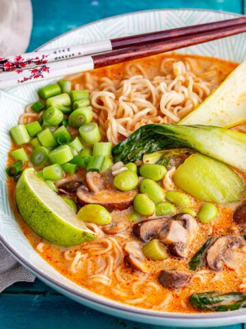 Bowl of noodle soup with lime and edamame and chopsticks