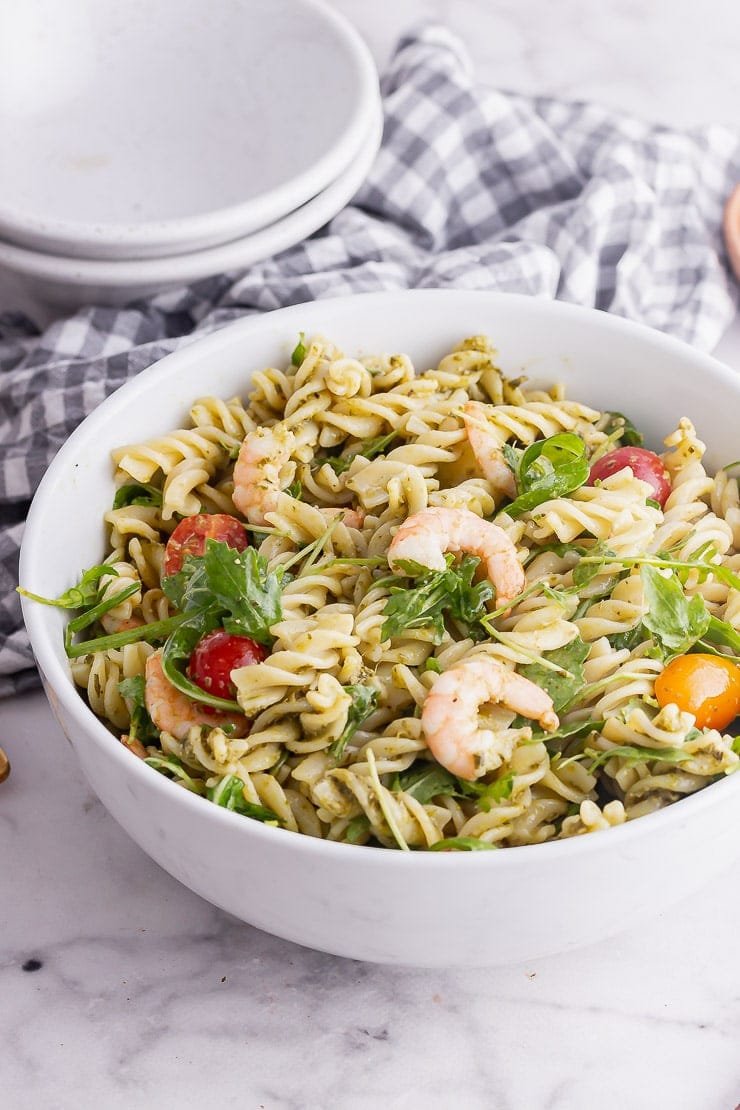 White bowl of pasta salad with pesto and prawns in front of a checked cloth