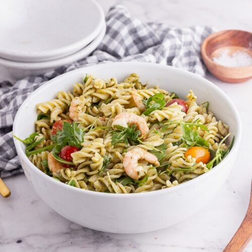 White bowl of pesto pasta salad on a marble background with a wooden spoon