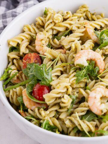 Close up of prawn pesto pasta in a white bowl