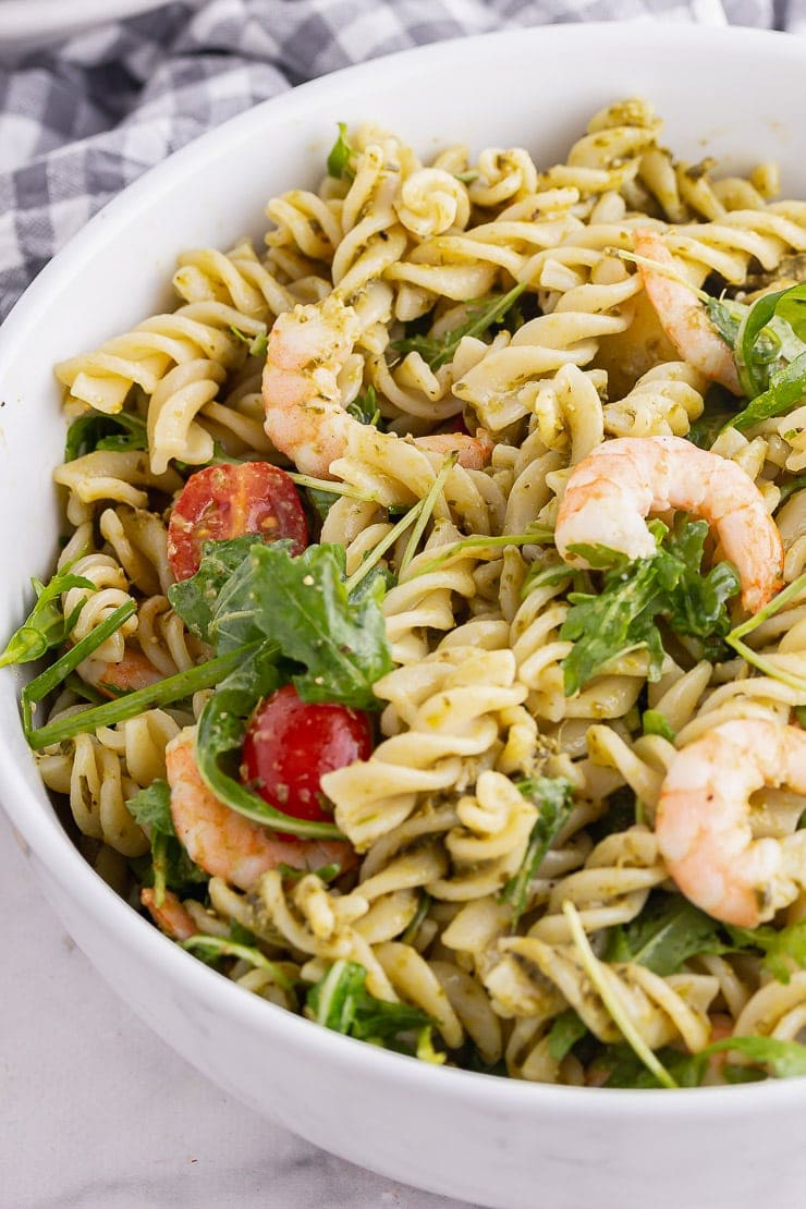 Close up of prawn pesto pasta in a white bowl