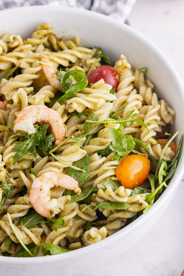 White bowl of shrimp pasta salad with pesto