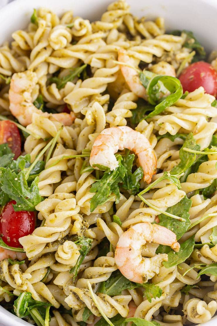Close up of prawns and pesto pasta with rocket and tomatoes