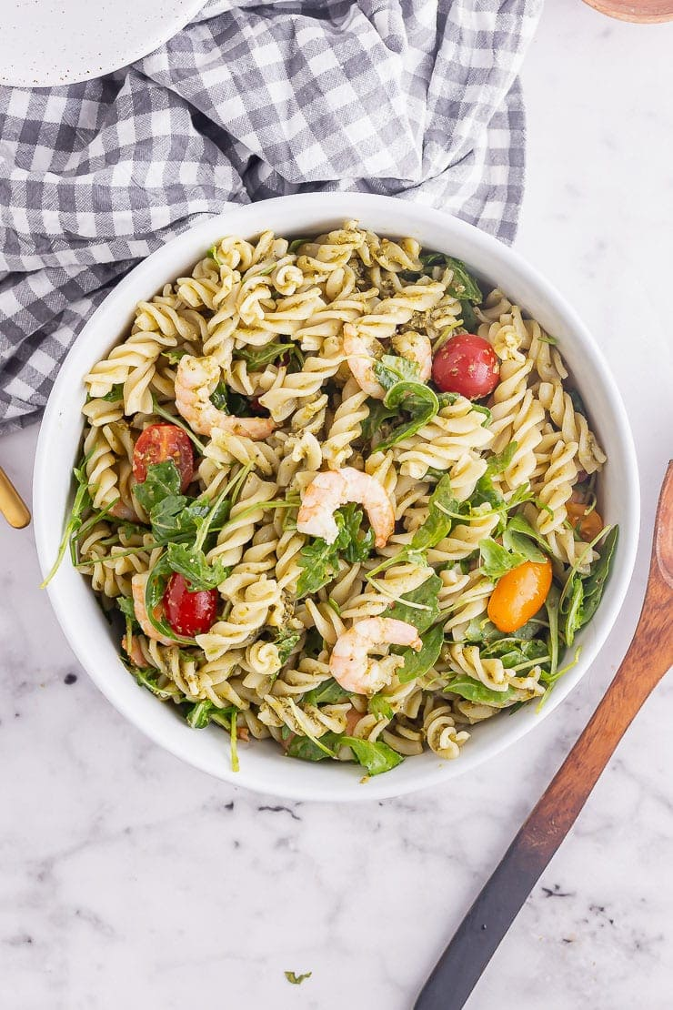 Overhead shot of prawn pasta with pesto in a white bowl on a marble surface