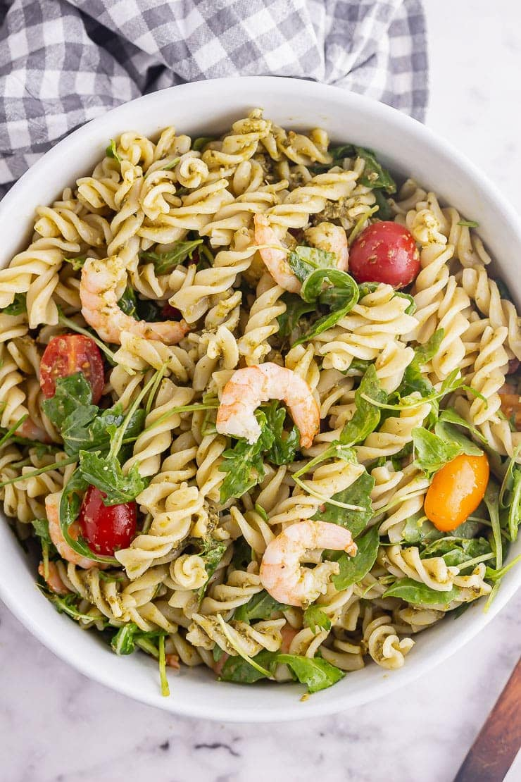 Overhead shot of prawn pesto pasta in a white bowl on a marble background
