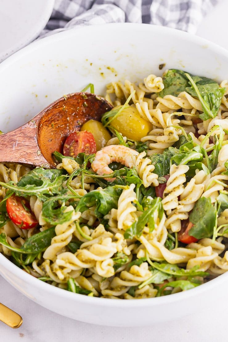 White bowl of pesto pasta salad with a wooden spoon