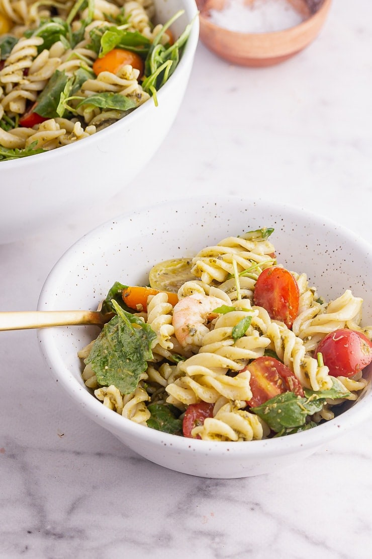 Small bowl of prawn pesto pasta with a gold fork