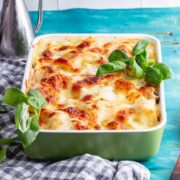 Side on shot of green baking dish of vegetarian lasagne with a checked cloth