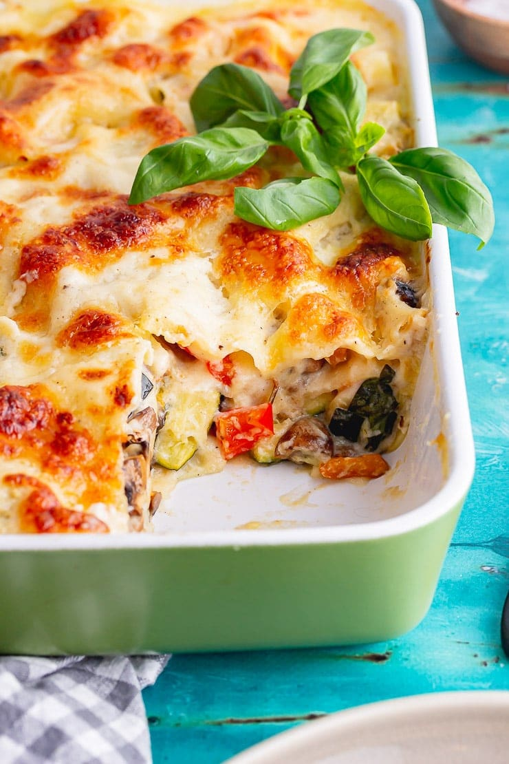 Veggie lasagne with a piece taken in a green baking dish