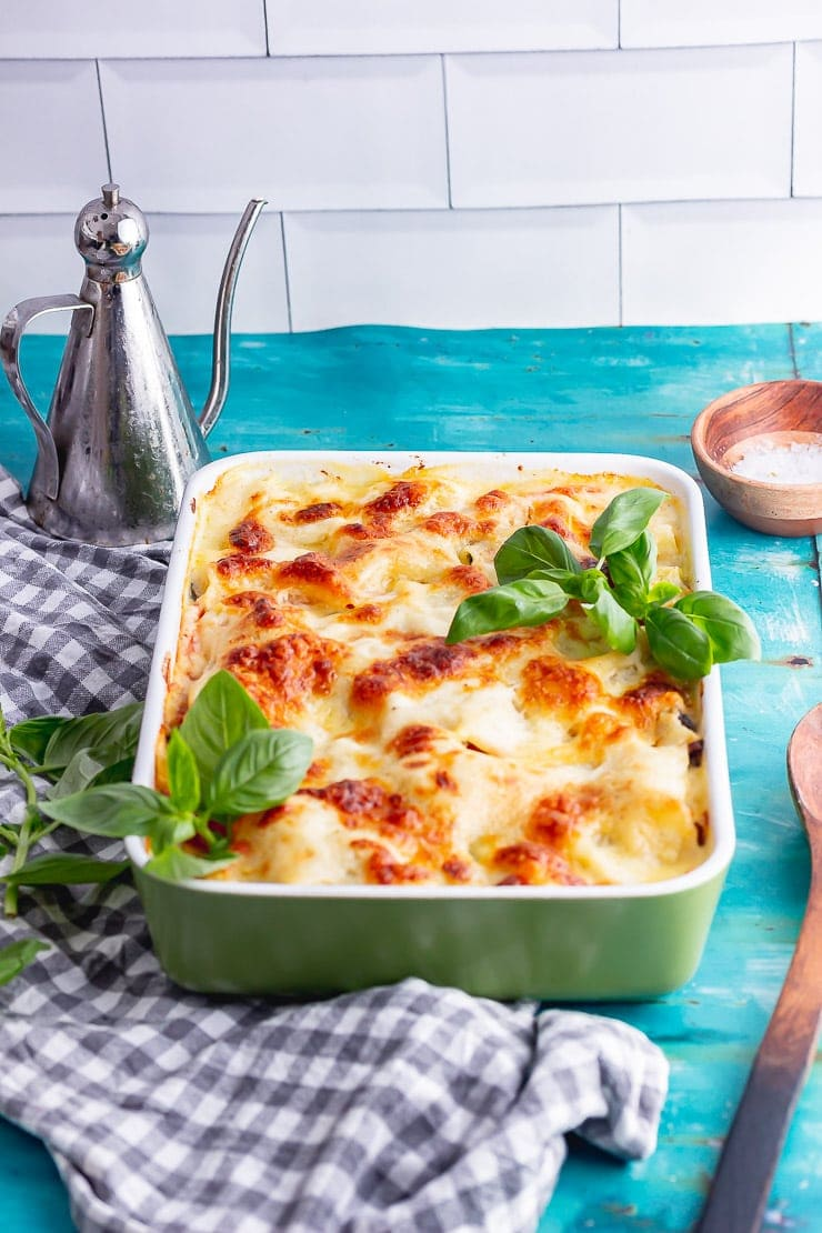 Side on shot of green baking dish of lasagne on a blue background