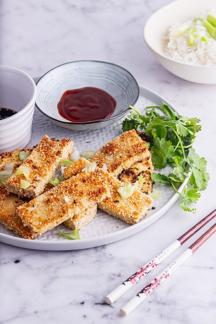 Grey plate of crispy sesame tofu with coriander on a marble surface
