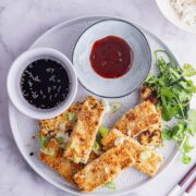 Grey plate of crispy fried tofu with sauce and herbs on a marble surface