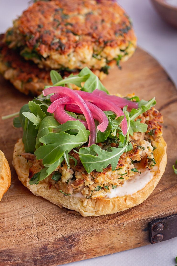Close up of tuna burgers topped with greens and pickled onions