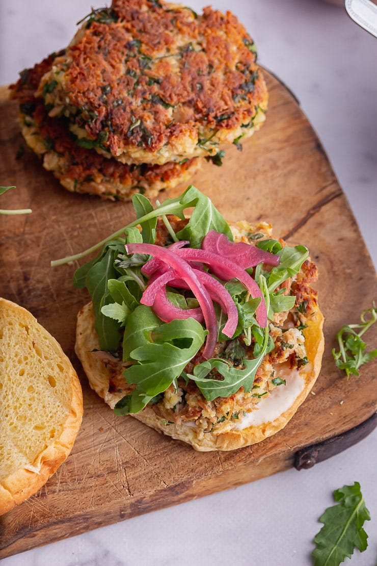 Tuna burgers on a board with greens and pickled onions