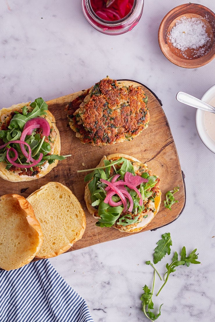 Overhead shot of tuna patties on a wooden board with a striped cloth