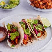 Grey plate of jackfruit tacos on a marble background