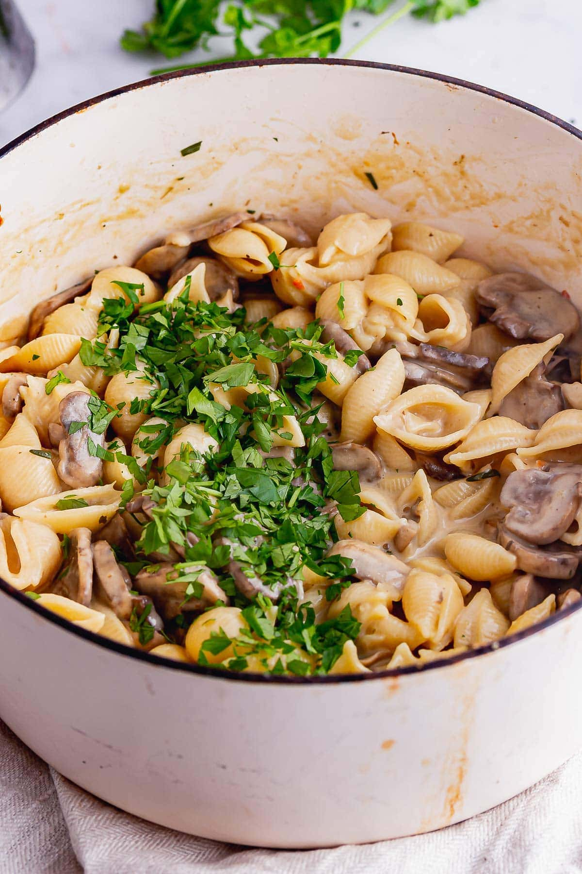 White pot of mushroom stroganoff topped with parsley