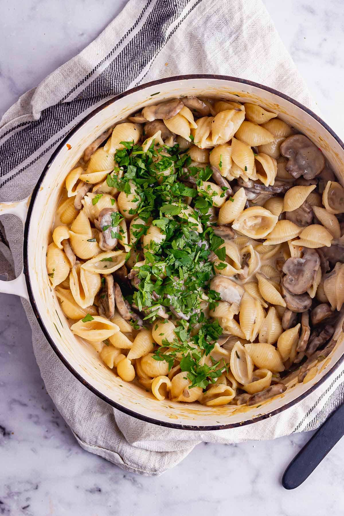 Overhead shot of creamy mushroom stroganoff on a cream cloth over a marble surface
