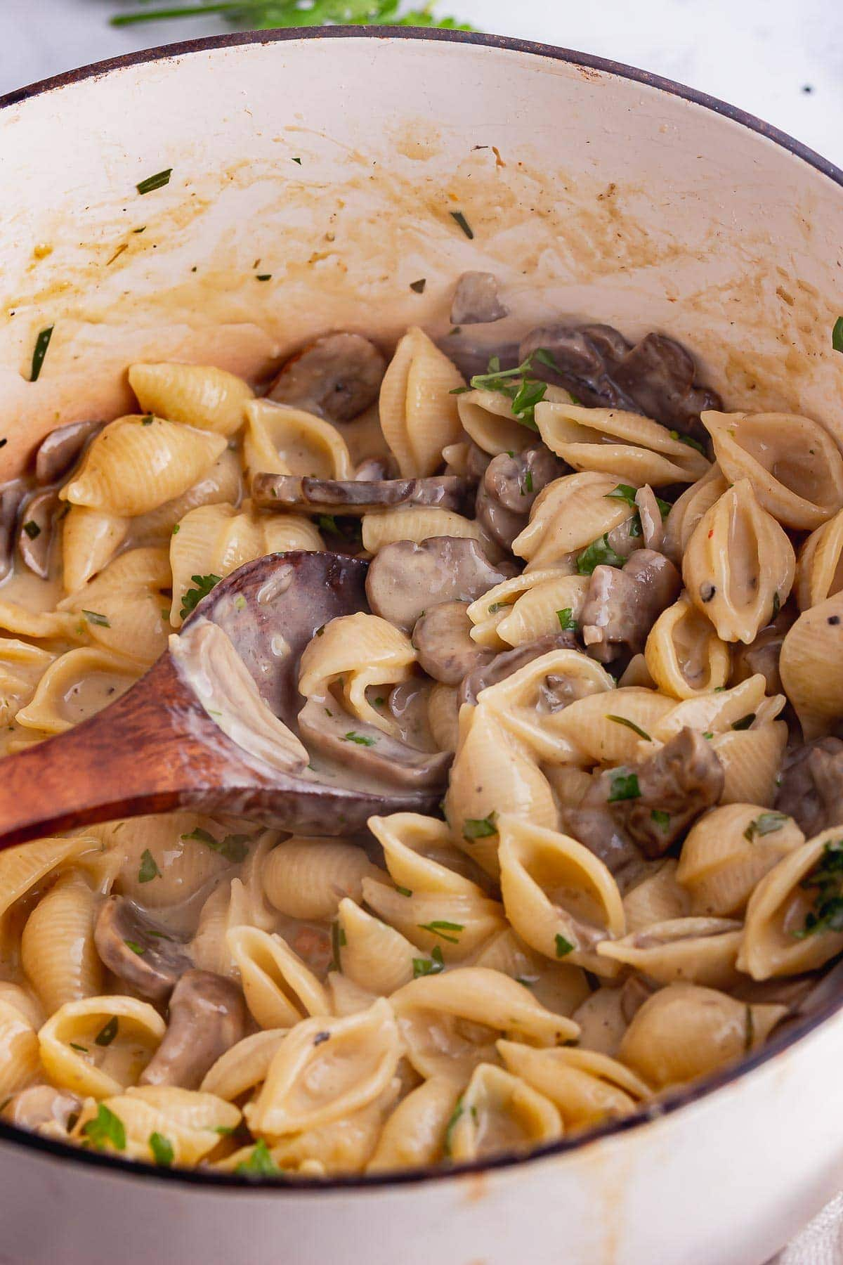 Wooden spoon in white pot of creamy mushrooms and pasta