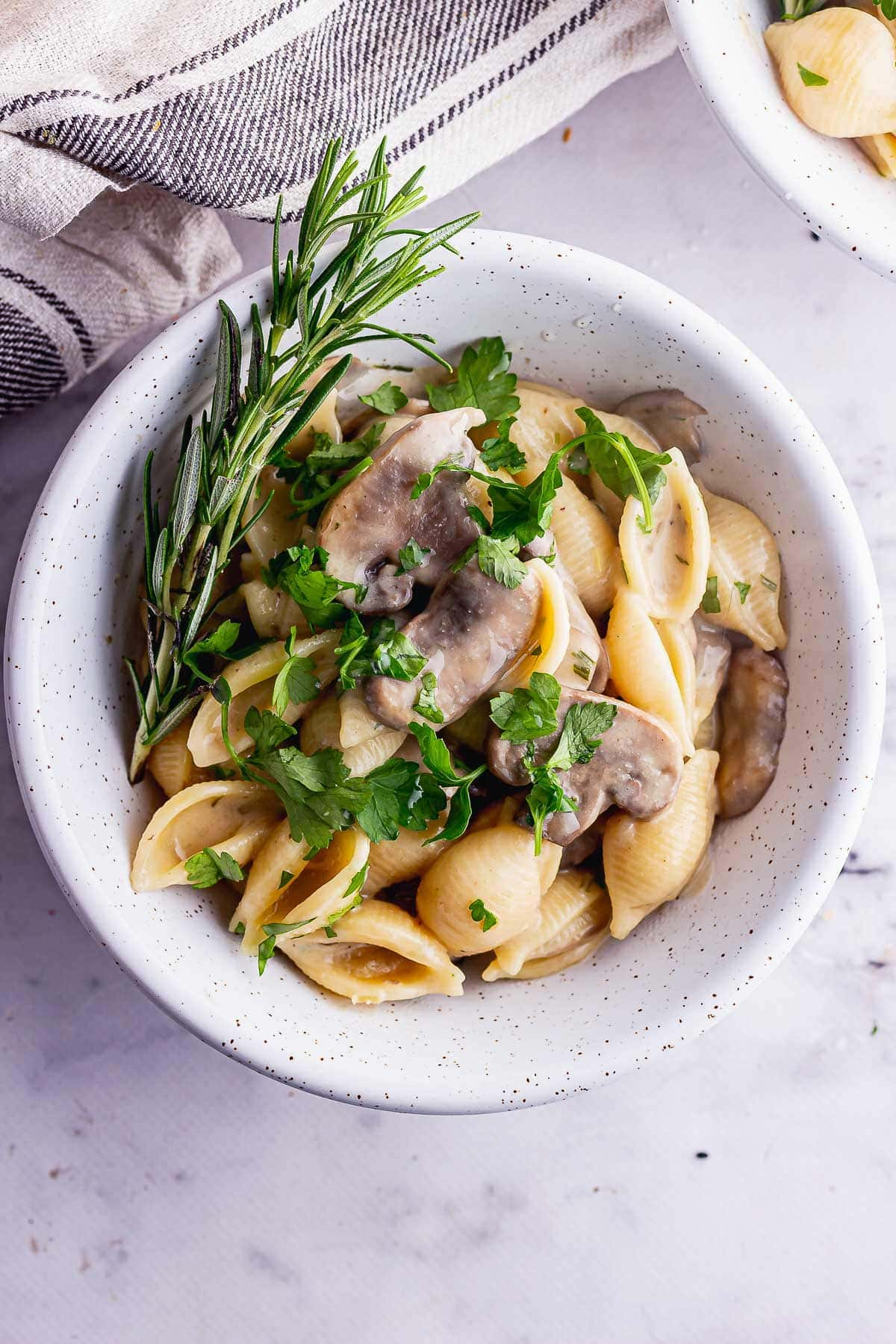 Overhead shot of creamy pasta and mushrooms with herbs