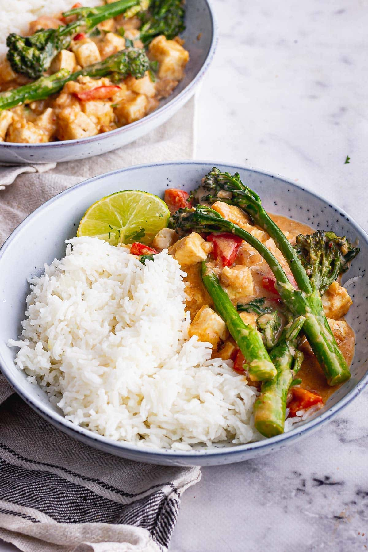 Blue bowl of veggie curry with peanut sauce and rice