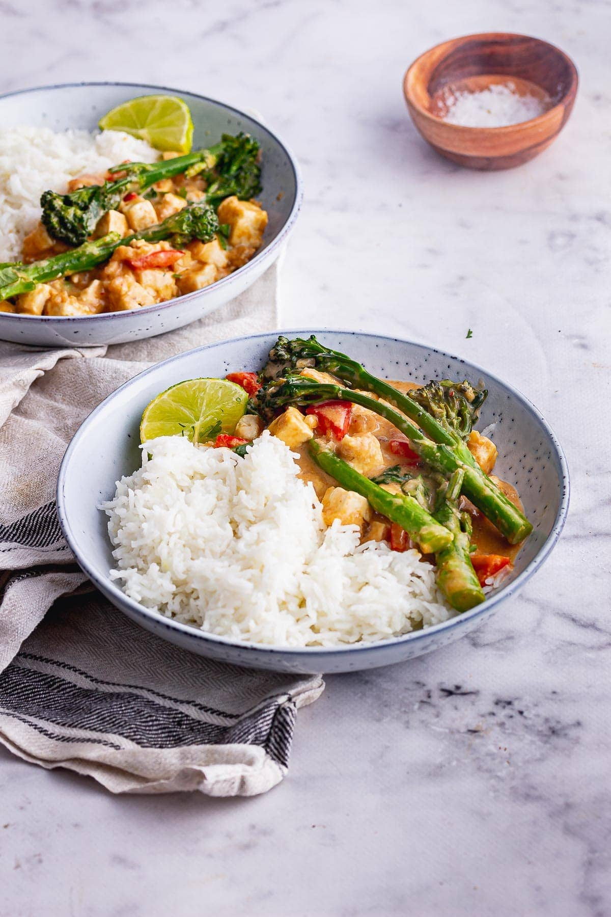 Blue bowls of peanut tofu curry with broccoli on a marble surface