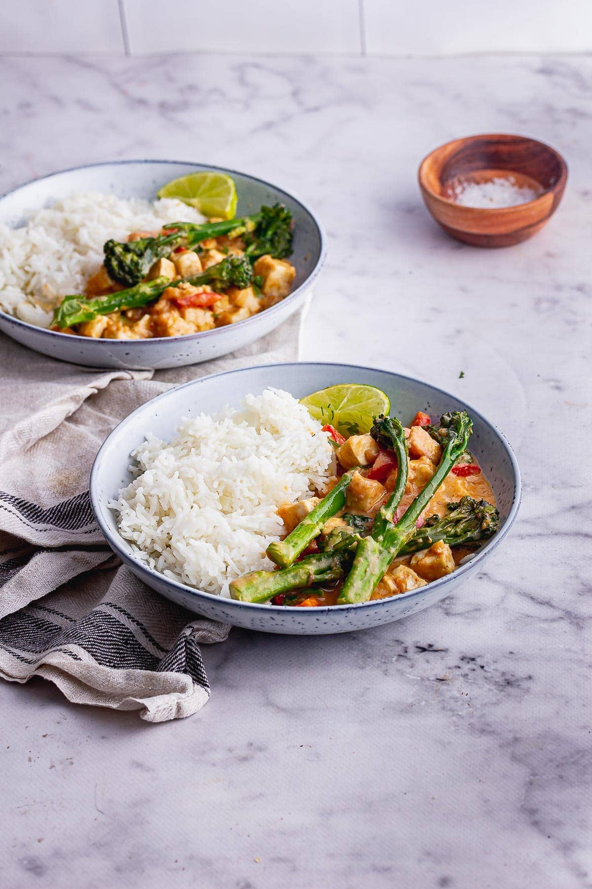 Blue bowls of peanut vegetable curry with rice on a marble surface
