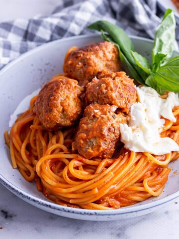 Close up of meatballs and spaghetti with mozzarella and basil