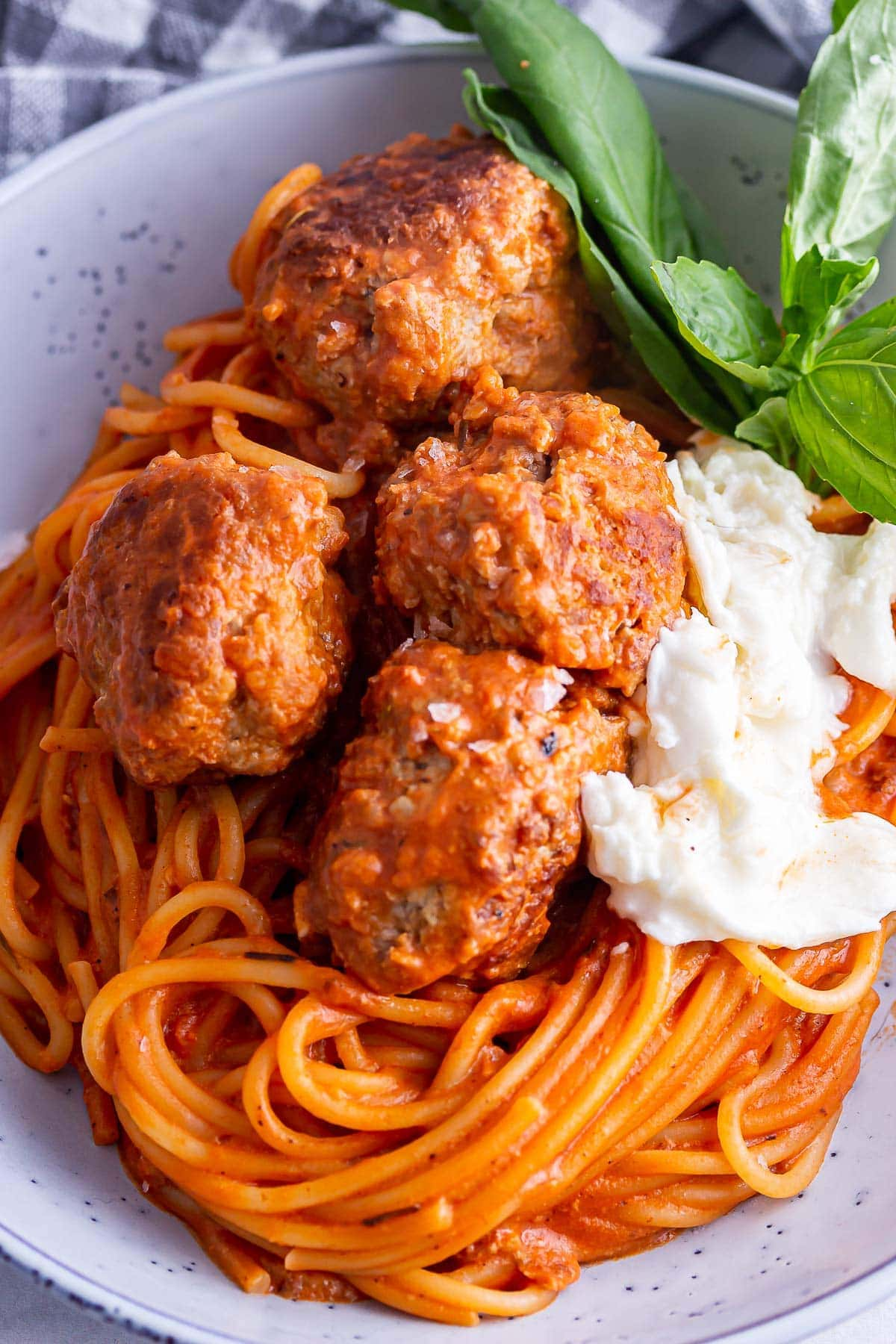Close up of meatballs on tomato spaghetti with mozzarella