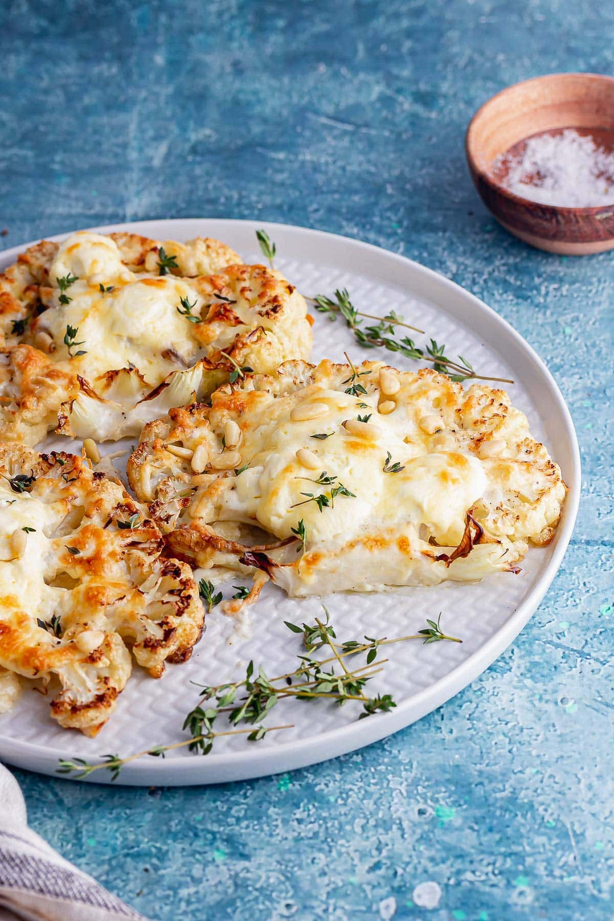 Side on shot of cauliflower steaks with thyme on a blue background
